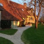 Sentier de gravier menant à l`entrée de la maison d`amis à deux étages avec surface habitable d`environ 160 m2.