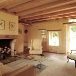 """Le salon (env. 27 m2) avec parquet en vieux chêne. La cheminée a été inspirée par celle de la cuisine et les murs ont été restaurés dans le style authentique de """"pierres apparentes""""."""